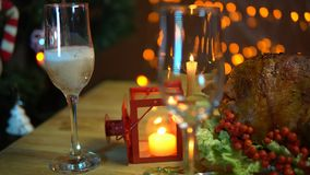 Christmas table setting with turkey. In the glass pour champagne next to the fried bird on a plate with a salad on the table on a background of yellow electric stock video