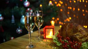 Christmas table setting with turkey. A roasted bird on a platter with a salad next to a glass of champagne stands on a table amidst yellow electric lights with stock video footage