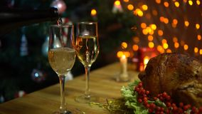 Christmas table setting with turkey. A roasted bird on a platter with a salad next to a glass of champagne stands on a table amidst yellow electric lights with stock footage