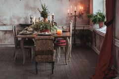 Christmas table setting. Vintage chairs, natural pine tree branches, candles. Rural or rustic style decorations.  stock images