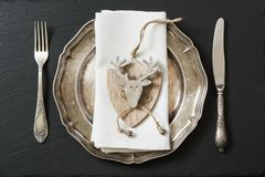 Christmas table setting with vintage dishware, silverware and deer decorations. Stock Photography