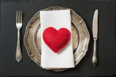 Christmas table setting with vintage dishware, silverware and heart decorations. Stock Photography