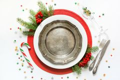 Christmas table setting with vintage dishware, silverware and red decorations on white background. Top view. Flat lay stock photos