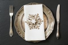 Christmas table setting with vintage dishware, silverware and snowflake decorations. Royalty Free Stock Photos