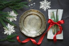Christmas table setting with vintage dishware, silverware and snowflake decorations on gray linen tablecloth. Top view Royalty Free Stock Photos