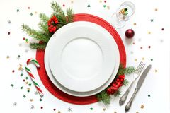 Christmas table setting with white dishware, silverware and red decorations on white background. Top view. Stock Image