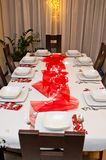 Christmas table setting with white plates and red decorations. Elegant table setting of Christmas theme with white plates and dishes and red decorations Stock Image
