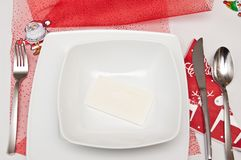 Christmas table setting with white plates and red decorations Stock Photos