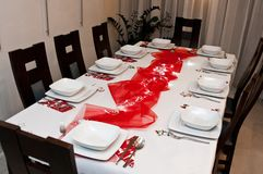 Christmas table setting with white plates and red decorations. Elegant table setting of Christmas theme with white plates and dishes and red decorations Royalty Free Stock Photo