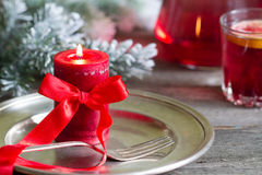 Christmas table with silver ware and red candle Stock Images