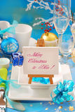 Christmas table with small easel. Christmas table decoration with greetings written on small easel standing  on the plate in blue and white color Stock Photography