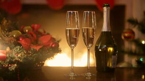 Christmas table with two glasses of champagne lit by burning fireplace at living room. Christmas table with glasses of champagne lit by burning fireplace at stock video footage