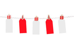 Christmas tags. Blank red and white Christmas tags hanging from silver line.  Ready for a message Royalty Free Stock Photography
