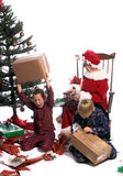Christmas Tantrum. A bratty child having a tantrum under the christmas tree while his brother and Mrs. Santa look on stock images