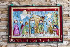 Christmas tapestry. Colored christmas tapestry hanging from a stone wall Stock Photography