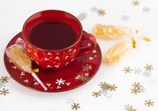 Christmas tea and crystal sugar. Black tea in a red mug, stick with crystal sugar and snowflakes Stock Photos