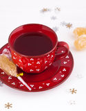 Christmas tea and crystal sugar. Black tea in a red mug, stick with crystal sugar and snowflakes Royalty Free Stock Photo