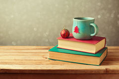 Christmas tea cup and ball on vintage books over blur background Royalty Free Stock Images