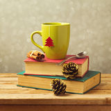 Christmas tea mug on books with decorations Stock Photos