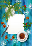 Christmas Tea Party Background. Holiday top view background with cup of tea, tree branches, blank paper sheet, ornament and star anise on wooden table Stock Photos