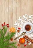 Christmas Tea Party Background. Holiday top view background with cup of tea, tree branches, Rosehip berries, orange, cinnamon sticks and star anise on wooden Royalty Free Stock Images