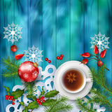 Christmas Tea Party Background. Holiday top view background with cup of tea, tree branches, Rosehip berries, ornament and star anise on wooden table Stock Photos