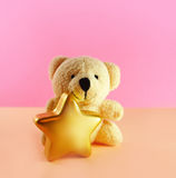 Christmas teddy bear. Teddy bear with christmas star on pink background stock photo