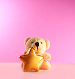 Christmas teddy bear. Teddy bear with christmas star on pink background royalty free stock images