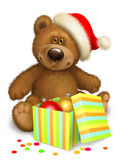 Christmas Teddy bear with box. Bear in the header of Santa Claus with box and balls Royalty Free Stock Images