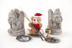 Teddy Bear with chopsticks and gargoyle. Royalty Free Stock Image