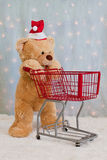 Christmas teddy bear pushing shopping cart Royalty Free Stock Images