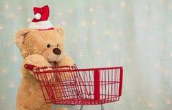 Christmas teddy bear pushing shopping cart stock photo