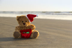 Christmas teddy bear sits on the beach. Goa, India Stock Photo