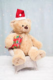 Christmas teddy bear sitting on chair Royalty Free Stock Photo