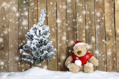 Christmas teddy bear sitting in the snow Stock Photos