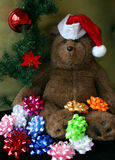Christmas Teddy Bear Wearing Santa's Hat. This is a Christmas teddy bear wearing Santa's hat surrounded by mulicolored bows an a christmas red ball Royalty Free Stock Images