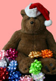 Christmas Teddy Bear Wearing Santa's Hat with Pink Background. This is a Christmas teddy bear wearing Santa's hat surrounded by mulicolored bows on a pink Royalty Free Stock Photos