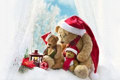 Christmas teddy bears sitting at the window in winter time Stock Photos