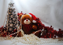 Christmas teddy 5. Christmas teddy with a silver star amongst red tinsel, white beads and a silver tree Royalty Free Stock Photos