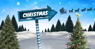 Christmas text on Wooden signpost in Christmas Winter landscape with Christmas tree and Santa`s slei. Digital composite of Christmas text on Wooden signpost in Stock Photo