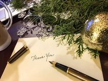 Christmas Thank You Card. Gold Fountain pen  on desk with christmas ornaments and evergreen tree gold and crystal writing thank you notes at the end of year for Royalty Free Stock Image
