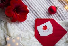 Christmas thankful greeting card in red envelope on white knitted plaid with Amaryllis flower, Christmas ball and glowing LED star.  royalty free stock photo