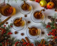 Mulled apple cider with spices: cinnamon sticks, cloves, anise on white table stock image