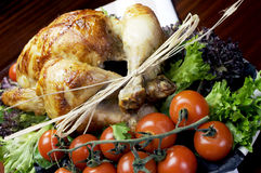 Christmas or Thanksgiving roast chicken turkey - Close up angle shot. Platter of delicious roast chicken turkey with salad greens and red tomatoes on the vine stock images