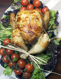 Christmas or Thanksgiving roast chicken turkey dinner -  Aerial. Platter of delicious roast chicken turkey with salad greens and red tomatoes on the vine for a Stock Image
