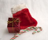 Christmas Theme. Classic christmas red stocking with little gift box and two candycanes stock images