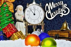 Christmas theme and atmosphere. Christmas time. The clock shows the long awaited moment. Coming Santa Claus and unpacking gifts un. Christmas time. The clock Stock Images