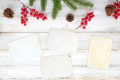 Christmas theme background with blank photo paper and decorating elements on white wood table. royalty free stock image