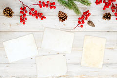 Christmas theme background with blank photo paper and decorating elements on white wood table. Royalty Free Stock Photo