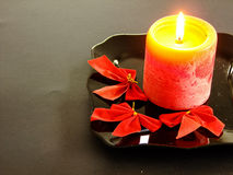 Christmas Theme Background. Christmas themed black Background with Candle on black Plate on right Side and some Ribbons Royalty Free Stock Image